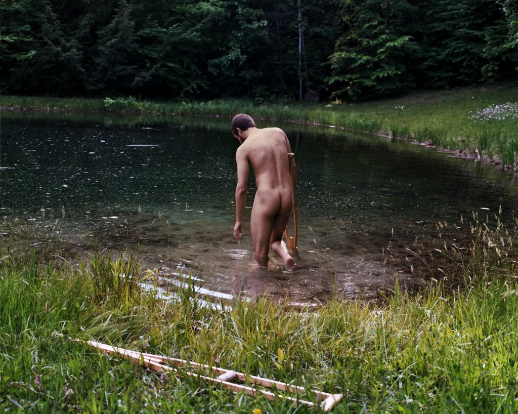 man stands in pond with crutch