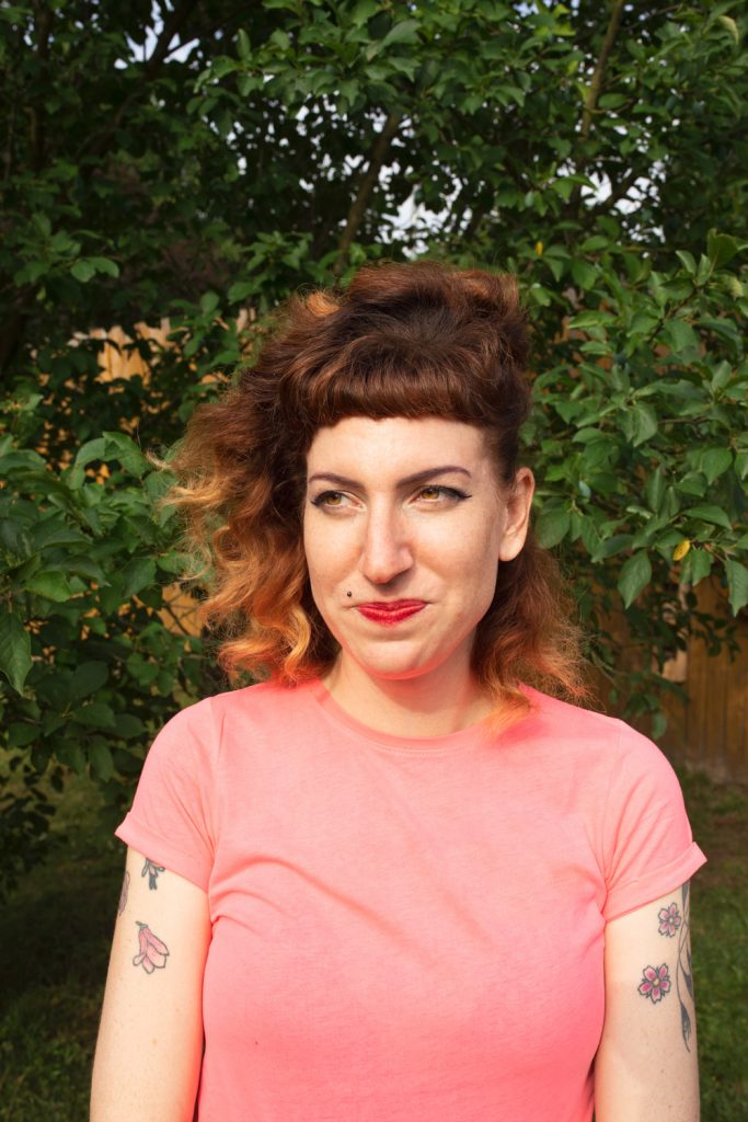 portrait of a woman with red hair and a pink shirt