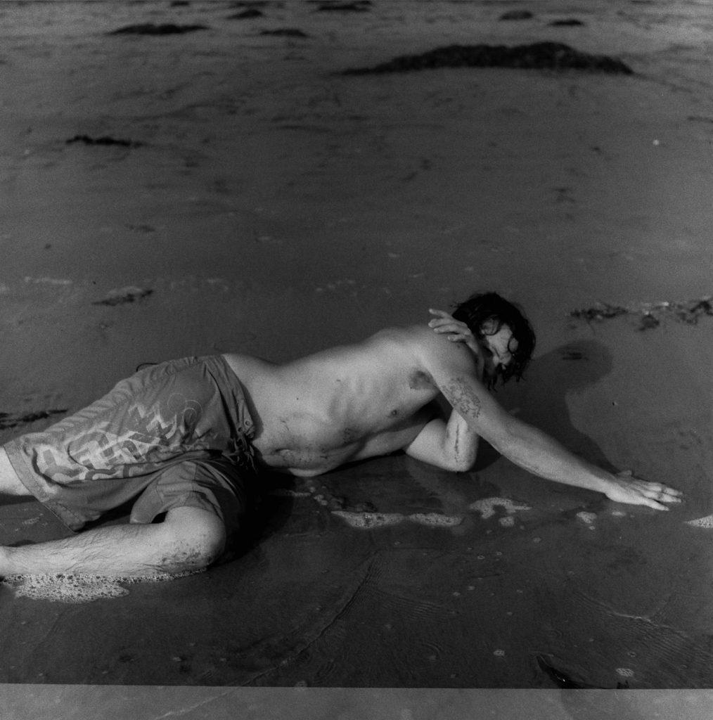 man reclining near pacific ocean
