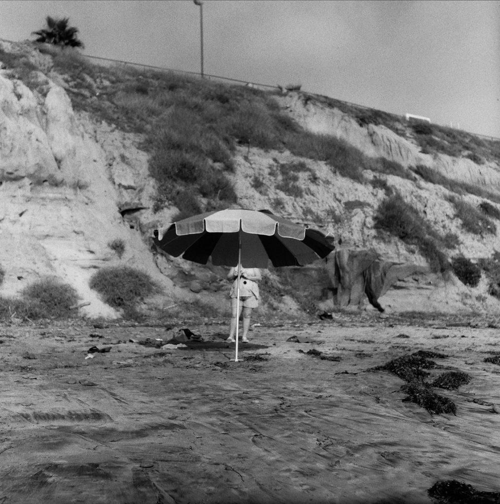 person standing behind a beach umbrella
